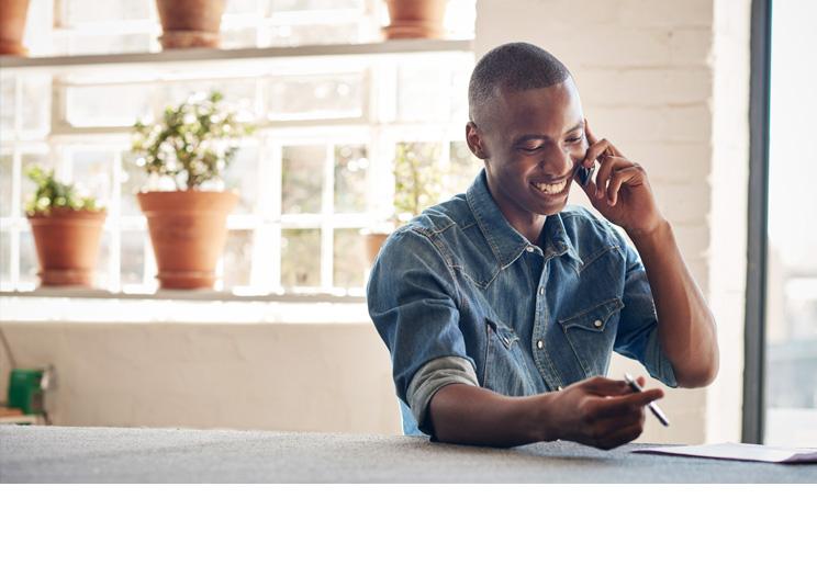 Izwe Ghana Savings for you   Personal Savings account   Man on phone at work   Square Image